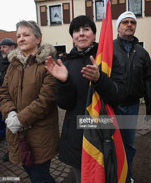 Supporters of the Alternative fuer Deutschland political party including one woman clutching a flag showing the Germany colors and common at Pegida...
