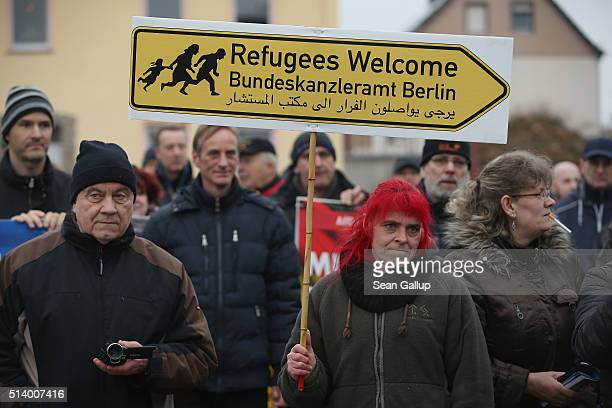 Supporters of the Alternative fuer Deutschland political party including one woman holding a sign with an arrow that reads 'Refugees Welcome Federal...