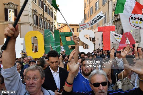 Supporters of the antiestablishment populist 5 Star Movement hold up letters of the alphabet that read Honesty during a protest outside the lower...