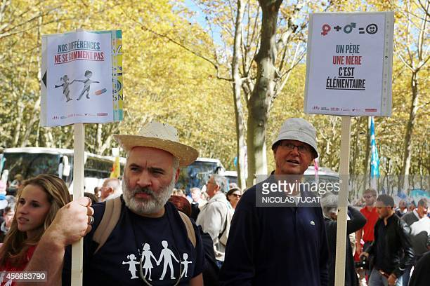 Supporters of the antigay marriage 'La Manif Pour Tous' movement hold signs reading 'One father one mother it's fundamental' and 'Our difference...