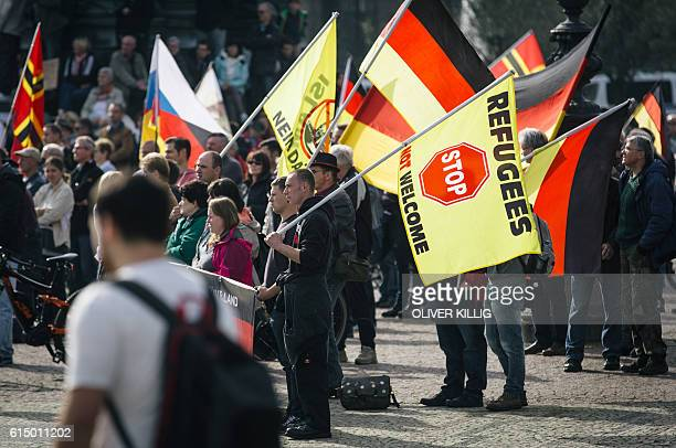 Supporters of the antiimmigrant Pegida movement mark the second year of existence as they demonstrate in Dresden eastern Germany on October 2016 and...