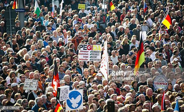 Supporters of the antiimmigrant Pegida movement mark their second year of existence as they demonstrate in Dresden eastern Germany on October 16 2016...