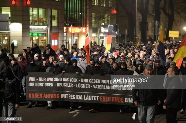 Supporters of the antiIslam 'Pegida' movement demonstrate holding a banner inscribed 'WIR NUR WIR SIND DAS VOLK UND GEBEN NUN DEN TAKT AN IHR DORT...