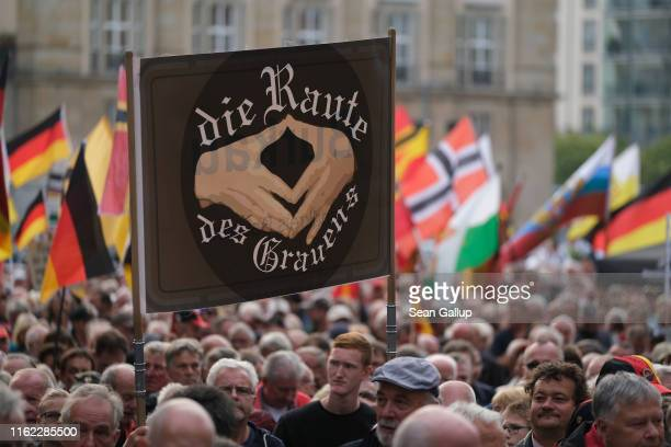 Supporters of the antiMuslim Pegida movement march with a sign ridiculing German Chancellor Angela Merkel and a hand gesture she often makes in their...