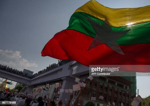 Supporters of the army wave a large Myanmar national flag during a large march in Yangon on October 29 2017 Military songs rang out across downtown...