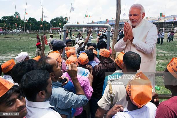 Supporters of the Bharatiya Janata Party stand in line near a paper cut out of Indian Prime Minister Narendra Modi at a rally in Muzaffarpur Bihar...