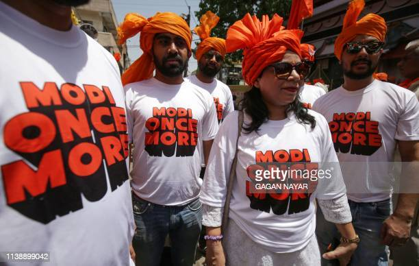 TOPSHOT Supporters of the Bharatiya Janata Party wear Tshirts supporting Indian Prime Minister Narendra Modi in Bhopal on April 23 2019 Some 190...