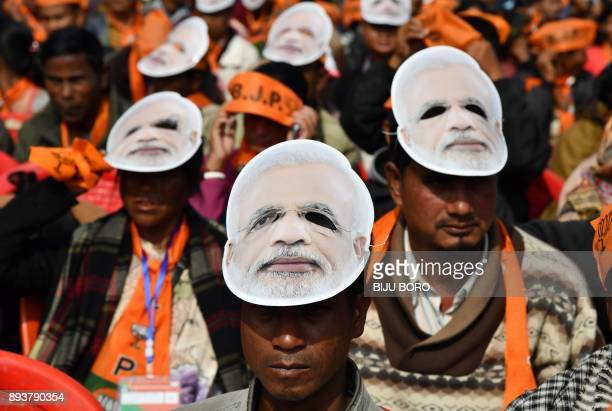 Supporters of the Bharatiya Janata Party , wearing masks of Indian Prime Minister Narendra Modi, listen to Modi during a public rally in Shillong on...