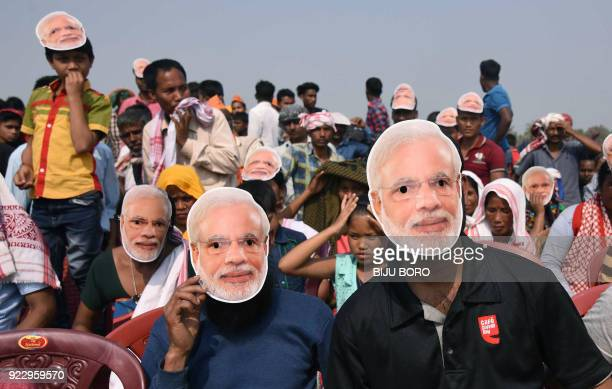 Supporters of the Bharatiya Janata Party wearing masks of Indian Prime Minister Narendra Modi listen to Modi during an election rally at Phulbari in...
