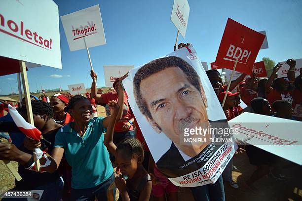 Supporters of the Botswana Democratic Party chant party songs and hold a placard with an image of incumbent Botswana President and leader of BDP...