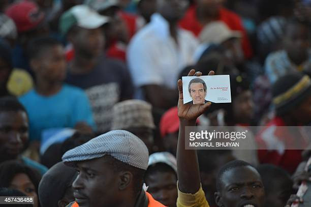 Supporters of the Botswana Democratic Party cheer and hold an image of incumbent Botswana President and leader of BDP Seretse Ian Khama as he...