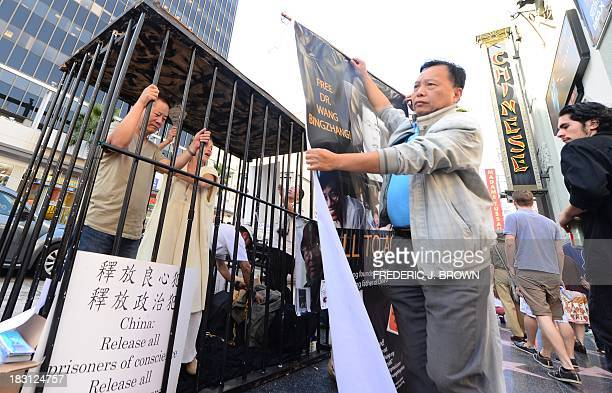 Supporters of the Chinese prodemocratic movement look on while voluntarily imprisoned in a cage in front of the TCL Chinese Theater formerly known as...