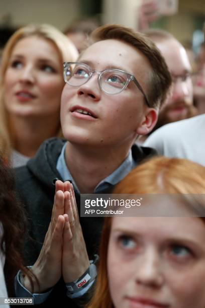 Supporters of the Christian Democratic Union watch as exit poll results were broadcasted on public television at an election night event at the...