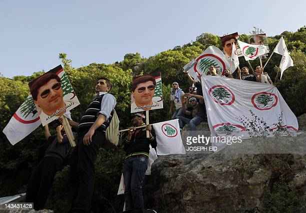 Supporters of the Christian Lebanese Forces party wave the party's flags and hold pictures of late Lebanese presidentelect Bashir Gemayel who was...