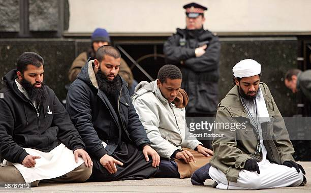 Supporters of the controversial Muslim cleric Abu Hamza alMasri are watched by British police officers as they pray outside of the Old Bailey...