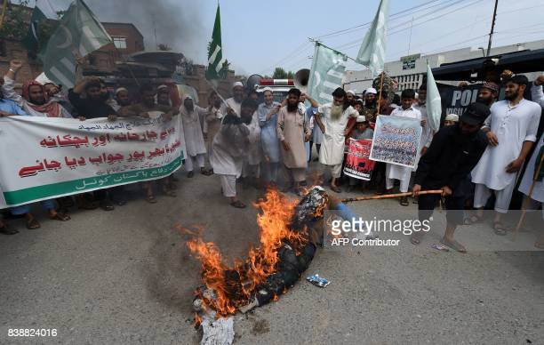 Supporters of the Defence of Pakistan Council a coalition of around 40 religious and political parties burn an effigy of US President Donald Trump...