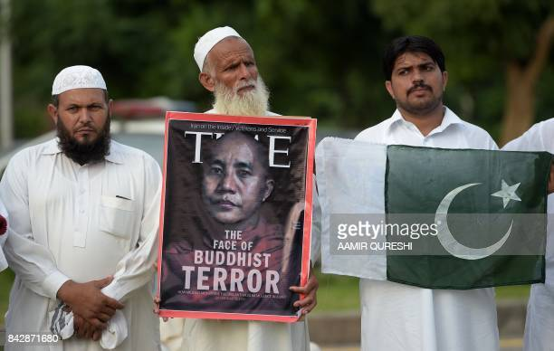 Supporters of the Defence of Pakistan Council carry a poster and the national flag during a protest in Islamabad on September 5 2017 against human...