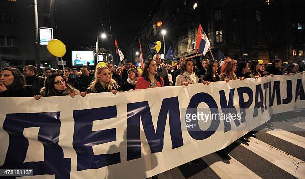 Supporters of the Democratic Party hold a banner reading Democracy as they march in downtown Belgrade on March 12 2014The Democratic Party the main...