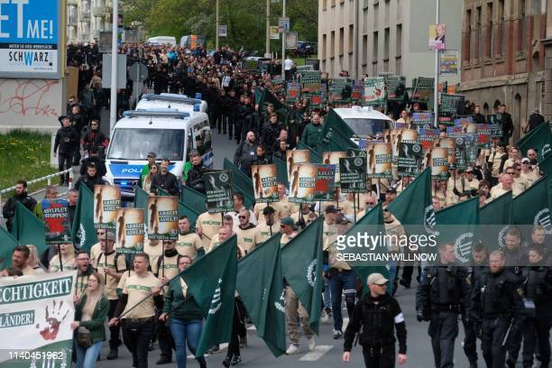 """Supporters of the """"Der Dritte Weg/Der III Weg"""" far-right and neo-nazi party walk through Plauen, eastern Germany, during a demonstration on Labour..."""