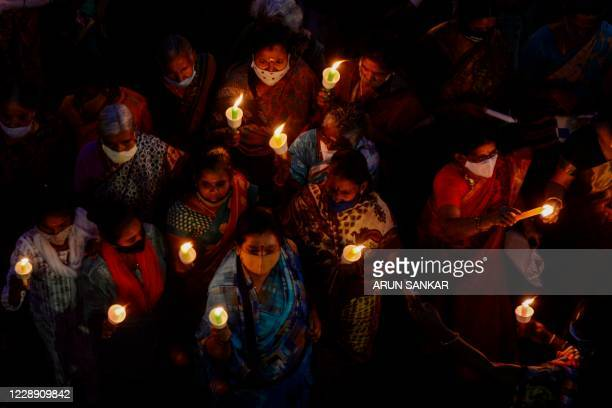 Supporters of the Dravida Munnetra Kazhagam party hold lit candles during a protest march to condemn the alleged gang-rape and murder of a...