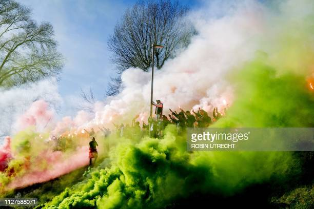 Supporters of the Dutch football team Feyenoord gather on February 26, 2019 at the training field to light flares and sing to the players prior to...