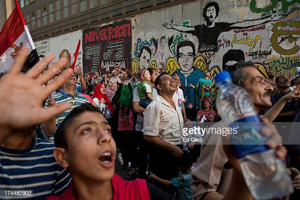 Supporters of the Egyptian Army watch a military helicopter fly low over a demonstration at Tahrir Square on July 26 2013 in Cairo Egypt Protesters...