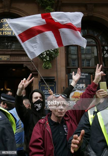 Supporters of the English Defence League wave a St George Cross flag during a rally and march by the farright group in central London on April 1 2017...
