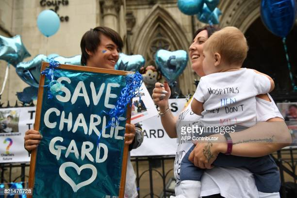 Supporters of the family of British baby Charlie Gard hold placards and signs of support outside the Royal Courts of Justice in London on July 24...