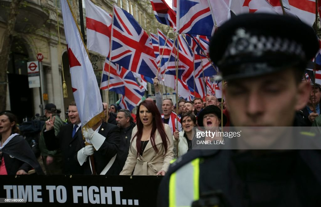 Supporters of the far-right group Britain First wave flags as they march and rally in central London on April 1, 2017 following the March 22 terror attack on the British parliament. Members of the Britain First group and the English Defence League rallied in central London in on seperate marches entitled a 'March Against Terrorism' and 'We Are Not Afriad' following the terror attack on Westminster Bridge and the British Parliament on March 22 which killed four people. The marches were opposed by the Unite Against Fascism organisation who held a static demonstration against the other groups. / AFP PHOTO / Daniel LEAL