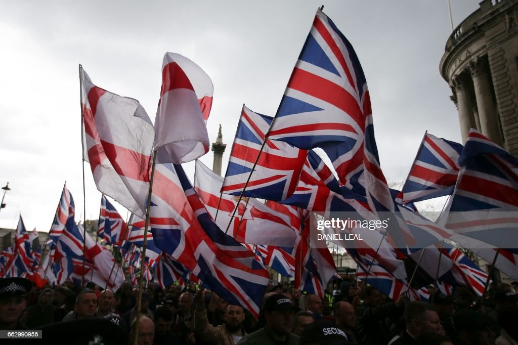 TOPSHOT - Supporters of the far-right group Britain First wave flags as they march and rally in central London on April 1, 2017 following the March 22 terror attack on the British parliament. Members of the Britain First group and the English Defence League rallied in central London in on seperate marches entitled a 'March Against Terrorism' and 'We Are Not Afriad' following the terror attack on Westminster Bridge and the British Parliament on March 22 which killed four people. The marches were opposed by the Unite Against Fascism organisation who held a static demonstration against the other groups. / AFP PHOTO / Daniel LEAL