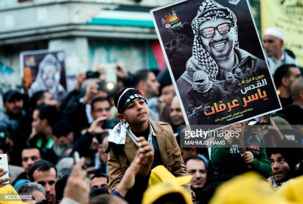 TOPSHOT Supporters of the Fatah movement hold up a portrait of late Palestinian leader Yasser Arafat during a rally in Gaza City on December 31...
