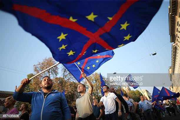 Supporters of the federalist and regionalist Italian political party Lega Nord and farright activists wave a flag of the European Union with a red...