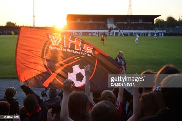 Supporters of the French third division football club Les Herbiers cheer their team during a French National 1 football match between Les Herbiers...