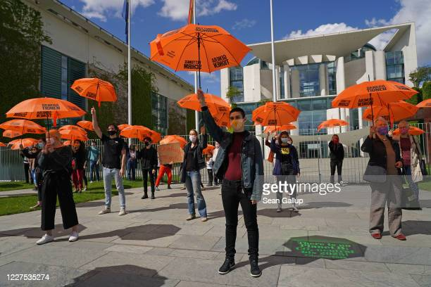 Supporters of the Generation Rescue Package campaign hold up orange umbrellas at the campaign's official launch in front of the Chancellery during...