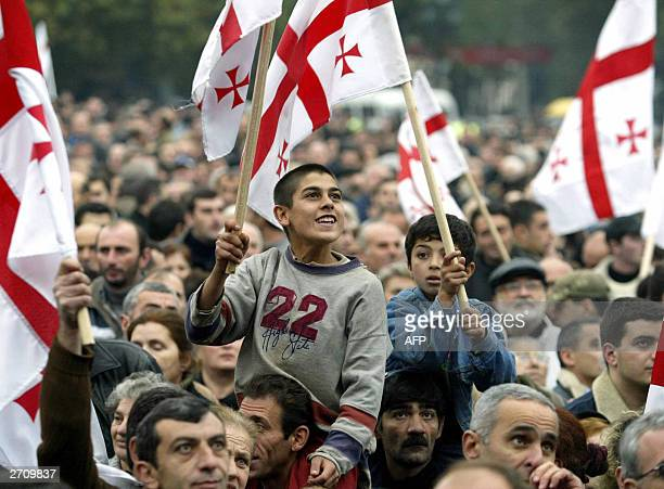 Supporters of the Georgian opposition wave flags during a protest rally in downtown Tbilisi 08 November 2003 About 10000 protesters staged a vigil in...