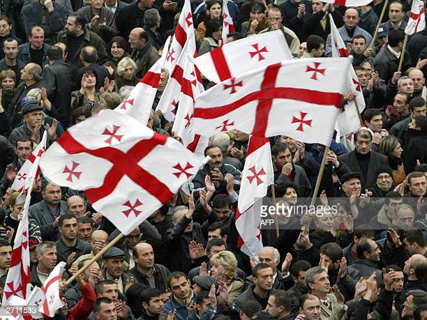 Supporters of the Georgian opposition wave party flags during a protest rally on the main square of Tbilisi 09 November 2003 Some 4000 protesters had...