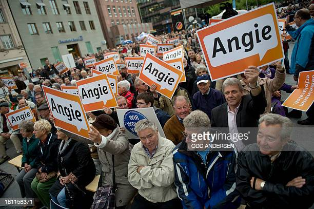 Supporters of the German Christian Democratic Union wave placards with Merkel's nick name as they await the arrival of German Chancellor Angela...