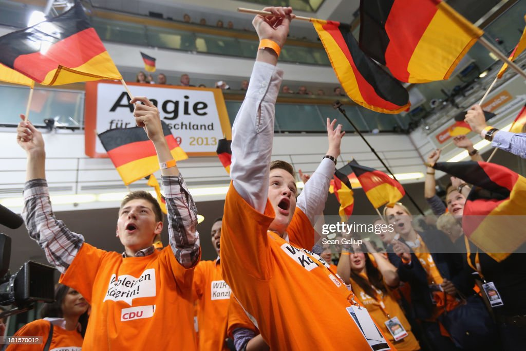 Supporters of the German Christian Democrats (CDU) wave German flags as they celebrate after inital election results give the CDU 42% of the vote in German federal elections on September 22, 2013 in Berlin, Germany. Germany is holding federal elections that will determine whether Chancellor Angela Merkel, who is also chairwoman of the CDU, will remain chancellor for a third term. Though the CDU has a strong lead over the opposition, speculations run wide as to what coalition will be viable in coming weeks to create a new government.