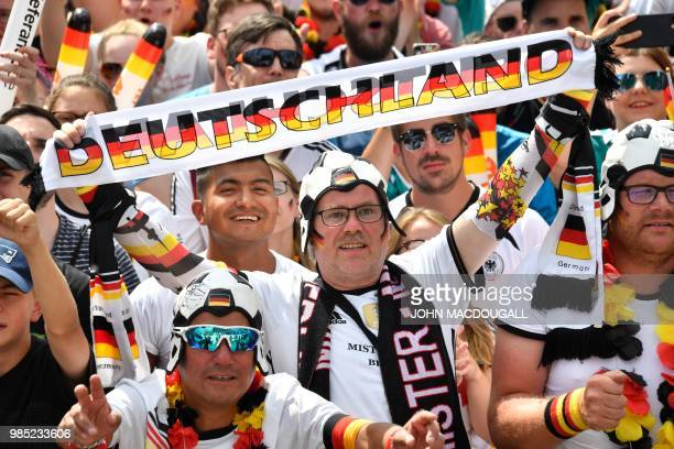 Supporters of the German national football team cheer as they attend a public viewing event at the Fanmeile in Berlin to watch the Russia 2018 World...