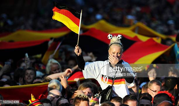 Supporters of the German national football team cheer with national flags during the public viewing at the 'Fanmeile' in front of Berlin's landmark...