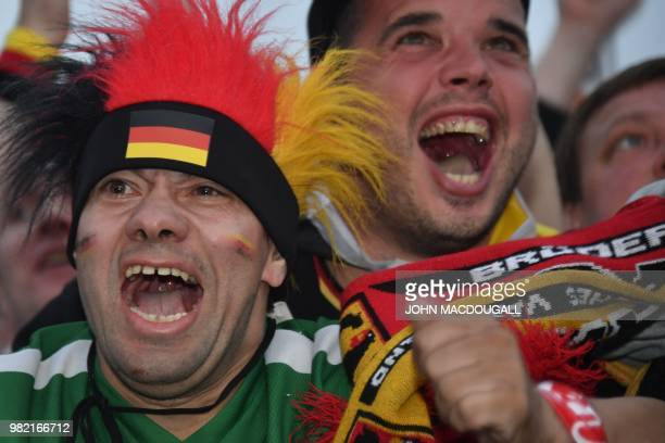 Supporters of the German national football team react after their team scored as they watch on a giant screen the Russia 2018 World Cup Group F...