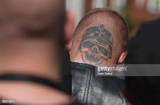 Supporters of the German radical right-wing party, the NPD, including a man with the tatoo of a helemted skull on the back of his head, listen to...