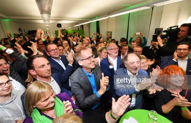 Supporters of the Green party react as first exit polls were announced on public television during the state elections in Hesse at the state...