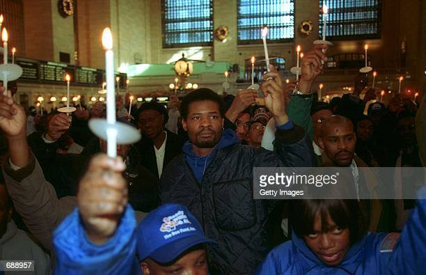 Supporters of the homeless and former homeless raise a candle at the Doe Funds sixteenth annual Christmas Day Candlelight Celebration in remembrance...