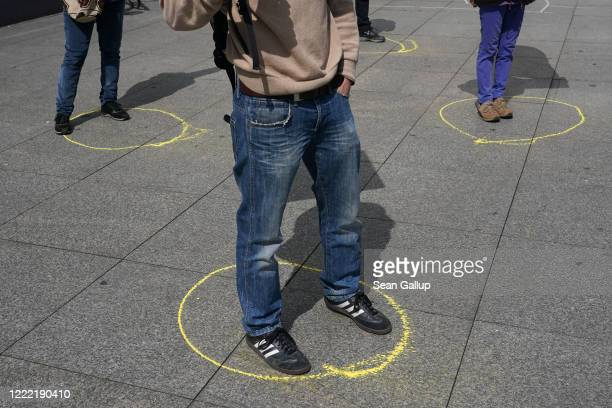 Supporters of the IG Metall labor union demonstrate while maintaining social distancing by standing in marked circles on May Day at Potsdamer Platz...