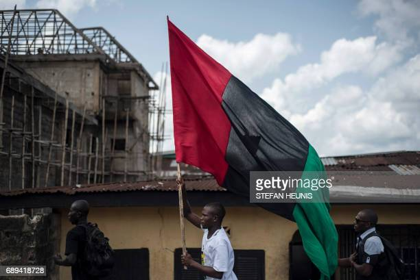 TOPSHOT Supporters of the Indigenous People of Biafra run with Biafran flags on May 28 2017 in the Osusu district of Aba The Nigerian civil wars 50th...