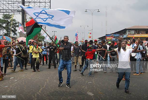 Supporters of the Indigenous People of Biafra wave an Israeli flag as they march in Port Harcourt on January 20 2017 in support of the US...