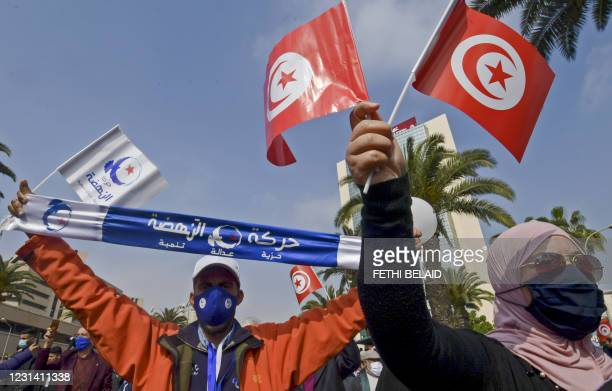 Supporters of the Islamist Ennahdha party wave flags during a demonstration in support of the Tunisian government on February 27, 2021 in the capital...
