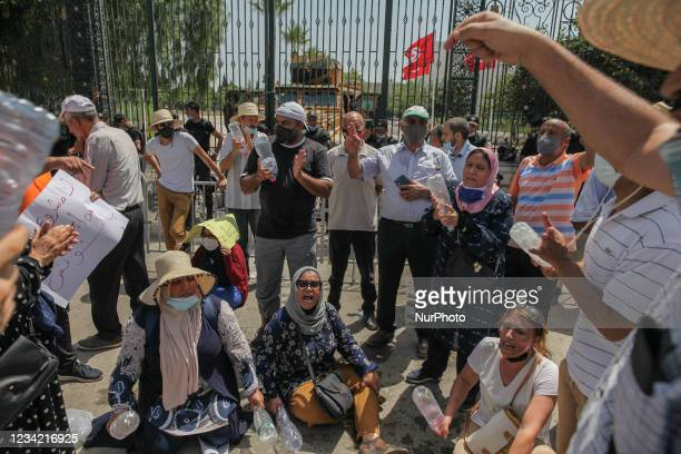 Supporters of the Islamist party Ennahdha chant slogans as they sit on the ground during a sit-in protest led by the Tunisian Parliament Speaker...