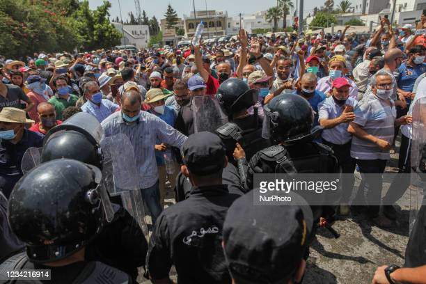 Supporters of the Islamist party Ennahdha clash with riot police during a sit-in protest led by the Tunisian Parliament Speaker Rached Ghannouchi, in...